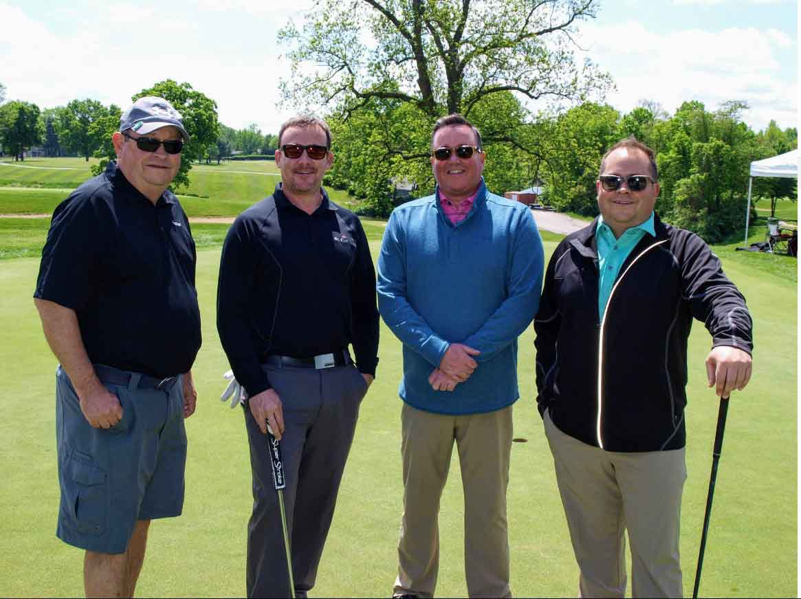 Four Men Standing on a Golf Course