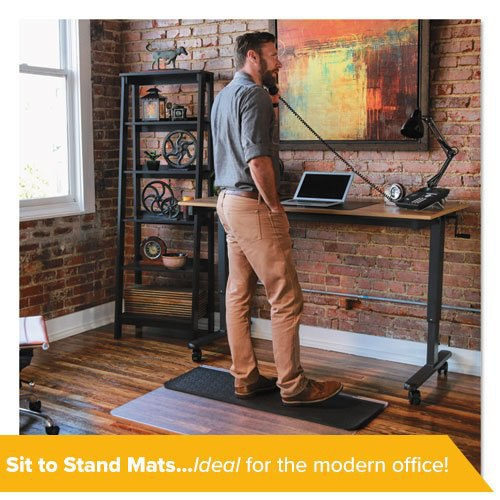 A man works in a modern office while standing on an ergonomic sit-to-stand mat.