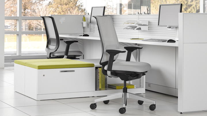 An open office with two personal desk spaces divided by lateral filing cabinets placed back to back.